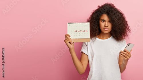 Cuadros en Lienzo Displeased dark skinned woman has unhappy look, holds periods calendar with mark