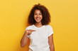 Smiling cheerful dark skinned girl points at herself, shows mockup space on white t shirt, happy being picked, models against yellow background. Carefree delighted young Afro woman asks who me
