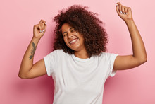 Funny Joyous Woman Raises Arms And Dances Carefree, Feels Pleasure And Amused, Laughs Happily, Eyes Closed From Satisfaction, Moves Along With Music, Has Tattoo Dressed In Casual Wear Isolated On Pink