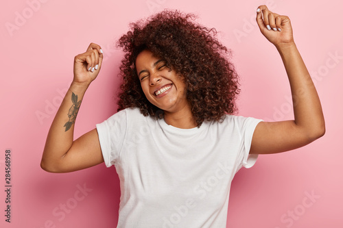 Funny joyous woman raises arms and dances carefree, feels pleasure and amused, laughs happily, eyes closed from satisfaction, moves along with music, has tattoo dressed in casual wear isolated on pink - 284568958