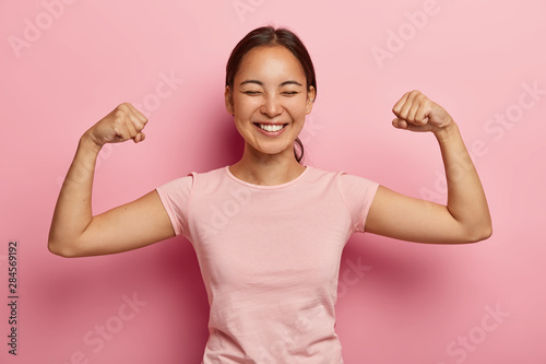 Fotografie, Obraz  Strong powerful Asian woman with dark combed hair, toothy smile, raises arms and shows biceps, has piercing in ear, wears casual rosy t shirt, models against pink background