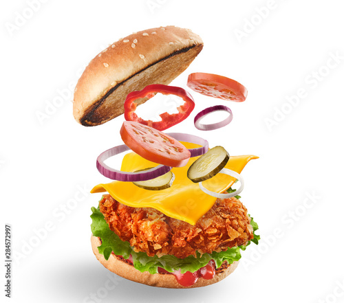 Fototapeta Burger with flying ingredients. Delicious monster Hamburger cheeseburger explosion concept flying ingredients.  Isolated on white obraz