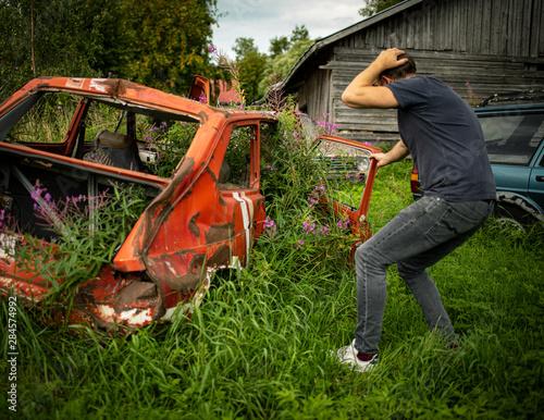Fotomural Mann wundert sich über Zugewachsenes Auto