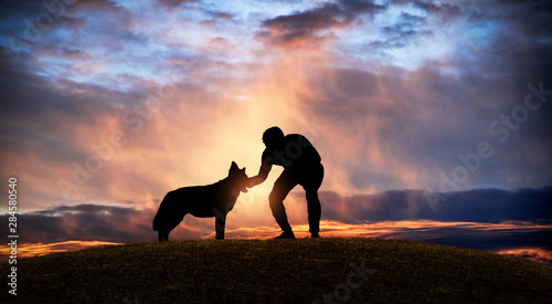Cuadros en Lienzo Silhouette of a man caressing his dog on a hill at sunset.