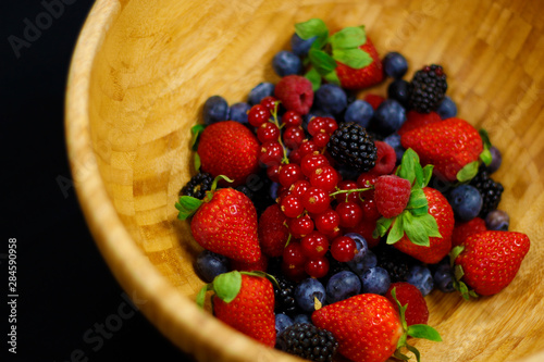 fresh berries fruit in wooden bowl includes strawberry, raspberry,blue berry,black berry etc.