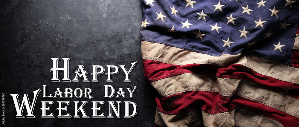 US American flag on worn black background. For USA Labor day celebration. With Happy Labor Day Weekend text.