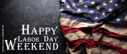 Photo Stands Countryside US American flag on worn black background. For USA Labor day celebration. With Happy Labor Day Weekend text.