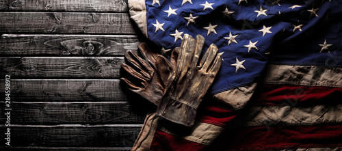 Leinwand Poster Old and worn work gloves on large American flag - Labor day background