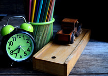 Wooden School Pencil Case, Alarm Clock, Color Pencils, Wooden Typewriter On An Old Wooden Table.