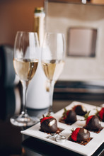 Elegant Wedding Rings On A Plate. Champagne With Starawberry On A Chocolate