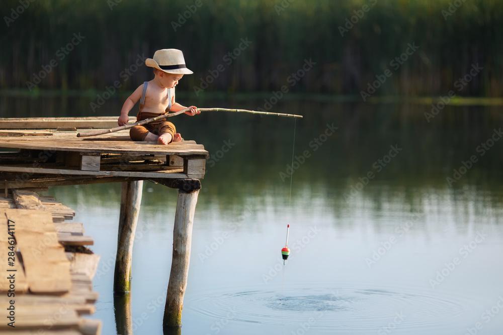 Fototapeta little boy fishing on the lake