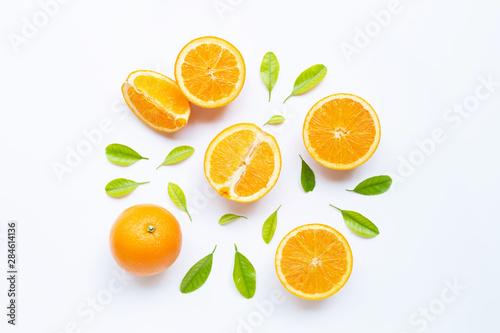 Obraz High vitamin C, Juicy and sweet. Fresh orange fruit with green leaves  on white. - fototapety do salonu