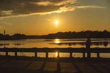 Silhouette Of Man Sitting On A Roadside Looking Out On A A Lake With Sunset.