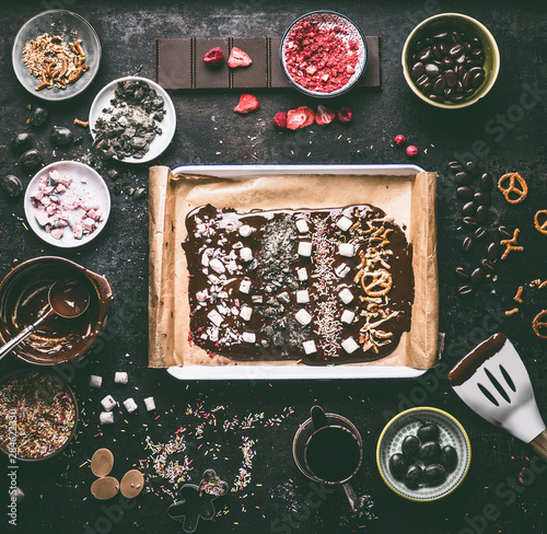 Fotografia  Preparation of homemade chocolate bark with various topping: melted chocolate in bowls , spatula, nuts, marshmallow, nuts, liquorice, caramel and candy on dark table