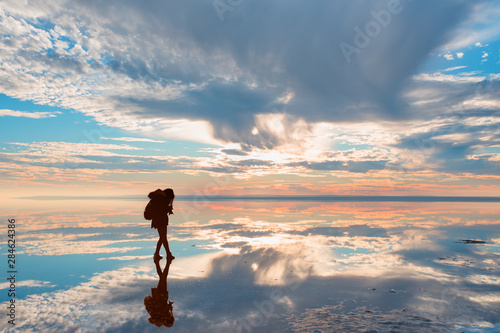 Fototapeta  Silhouette of photographer takes a photo at amazing sunset with reflected waters