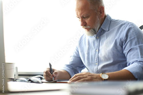 Canvastavla  Mature businessman looking and analyzing document in his modern office at work