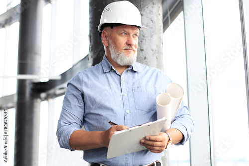 Obraz Confident mature business man in hardhat holding blueprint and looking away while standing indoors. - fototapety do salonu