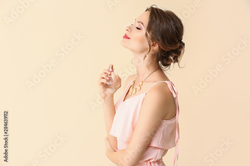 Beautiful young woman with bottle of perfume on light color background Wallpaper Mural