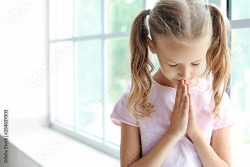 Praying little girl near window Canvas Print
