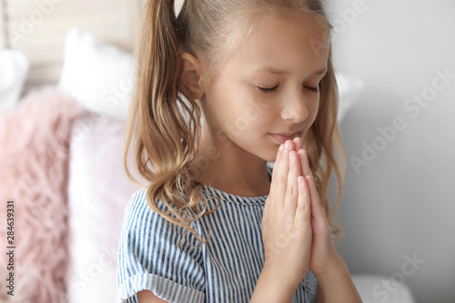 Foto  Cute little girl praying in bedroom