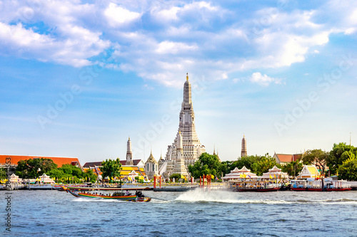 Wat Arun Temple with long tail boat in Bangkok Thailand.