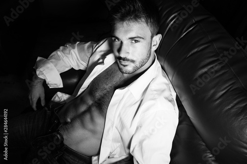 Fotomural  Portrait of attractive young man with beard and open shirt revealing sixpack abs