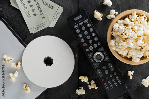 Fotografía DVD or blu ray movie disc with tv remote control, movie tickets and bowl of popcorn on dark background