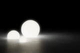 Three warm glowing sphere light objects on shiny modern industrial concrete floor in dark room with copy space - 3D illustratrion