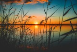 Fototapeta  - Beautiful scenic view of the red sunset over a lake