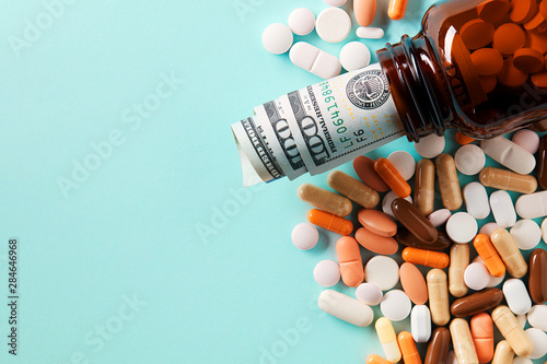Fototapeta USD dollar bills in a drug bottle over the medical pills. Medicine, healthcare industry and drug trafficking concept. Overhead macro view with copy space. obraz