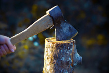 An Old Axe With A Wooden Battered Handle And A Worn Edge Cut A Large Thick Log Into Pieces, From Which Small Chips Fly Off.
