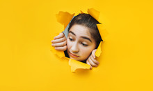Teenage Girl Peeping Through Hole On Yellow Paper. The Concept Of Surprise, Joyful Mood From What He Saw. Discounts, Sales, Surprise. Copy Space.