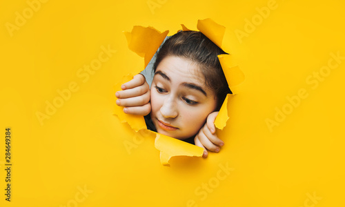 Fototapeta Teenage girl peeping through hole on yellow paper. The concept of surprise, joyful mood from what he saw. Discounts, sales, surprise. Copy space. obraz