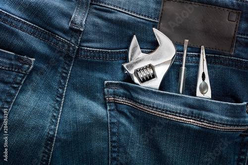 Fotografie, Obraz  Adjustable wrench, pliers and screwdriver in the back pocket of a blue jean