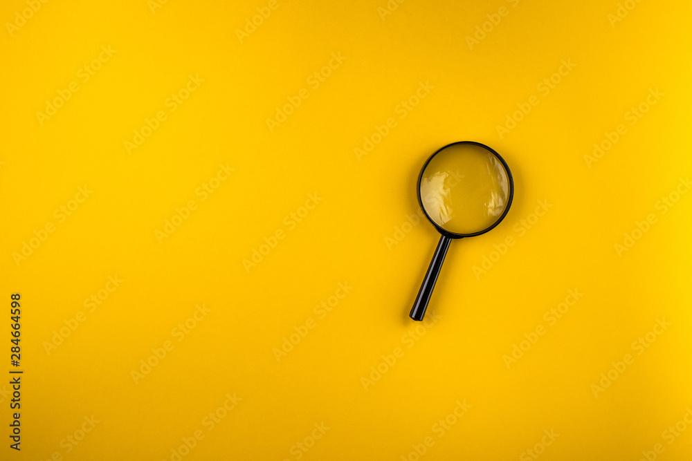 Fototapeta magnifying glass on yellow background