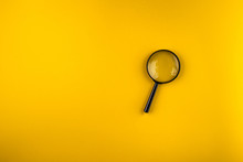 Magnifying Glass On Yellow Bac...
