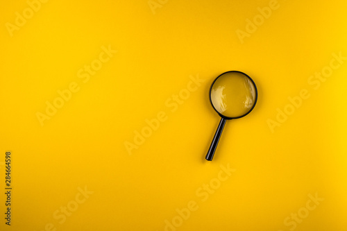 Fotografia  magnifying glass on yellow background