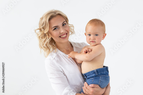 obraz PCV Single parent, motherhood and babyhood concept - Mother holding sweet baby girl on white background