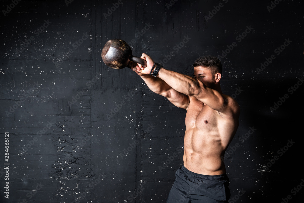 Fototapeta Young strong sweaty focused fit muscular man with big muscles holding heavy kettle bell for swing training hard core workout in the gym