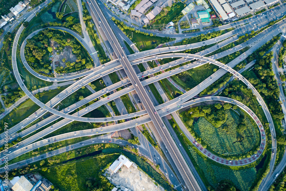Fototapety, obrazy: Aerial view of road interchange or highway intersection with busy urban traffic speeding on the road. Junction network of transportation taken by drone.