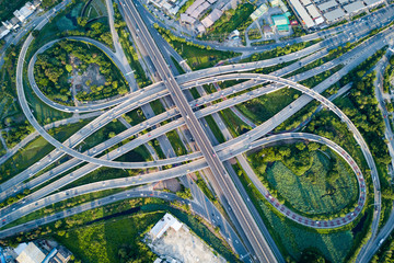 Aerial view of road interchange or highway intersection with busy urban traffic speeding on the road. Junction network of transportation taken by drone.