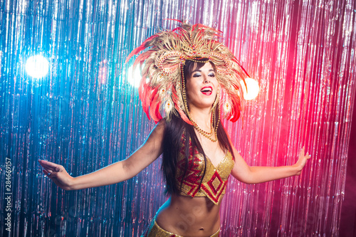 Fotografie, Obraz  Carnival, dancer and holiday concept - Beauty brunette woman in cabaret suit and headdress with natural feathers and rhinestones