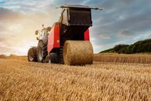 Farmer In Fields Making Straw Bales