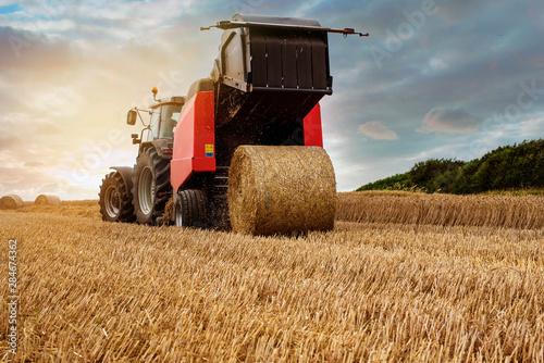 Photo farmer in fields making straw bales