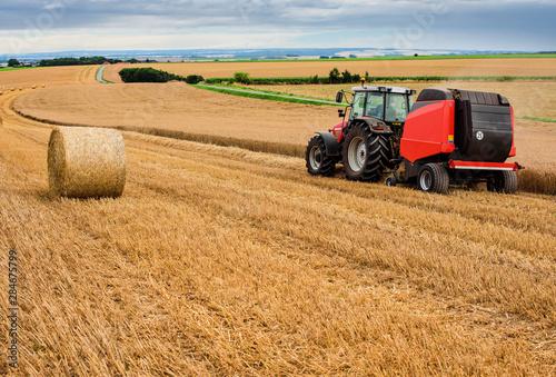 farmer in fields making straw bales Fototapet