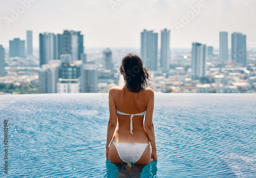Young beautiful woman relax in swimming pool on rooftop and enjoy cityscape Fotobehang