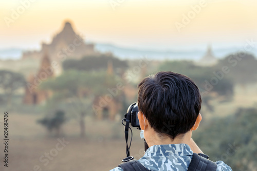 Photo Back wiew of tourists admire and take photography while the sun sets at the anci