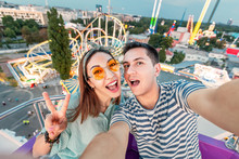Loving Mixed Race Couple Hugging And Riding On The Ferris Wheel And Take A Selfie Photo During The Weekend At The Amusement Park. Date And Relationship