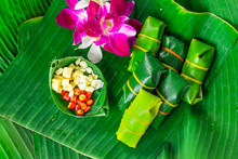 Traditional Thai Food Style Sour Porks Wrapped With Banana Leaf Decorated With Ingredient Orchid Flower, Top View