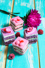 Pink And Purple Little Desserts On A Blue Background With Flowers
